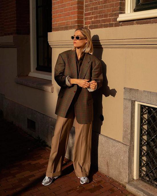 Девушка в широких бежевых брюках, пиджаке оверсайз в клетку и кроссовках