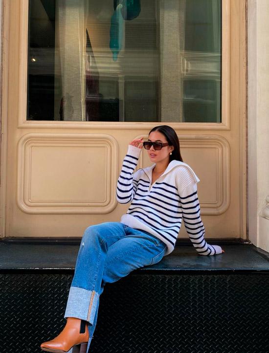 Девушка в синих джинсах, светлом свитере в полоску и ботильонах