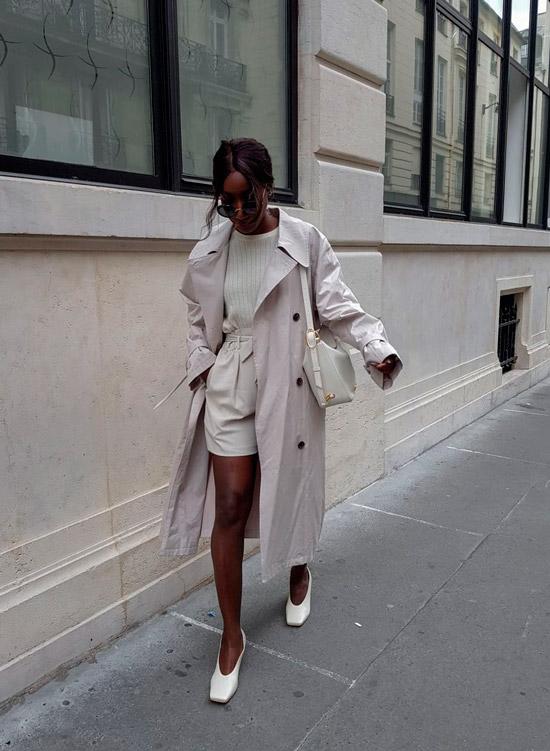 Девушка в светлых шортах, бежевом плаще и туфлях