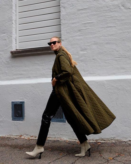 Девушка в зеленом стеганном пальто, черных брюках и ботильонах
