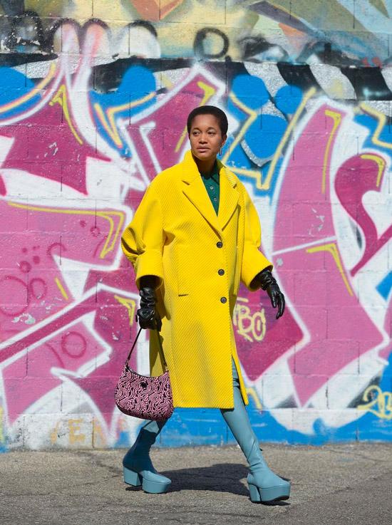 Девушка в желтом пальто с объемными рукавами и голубых сапогах на платформе