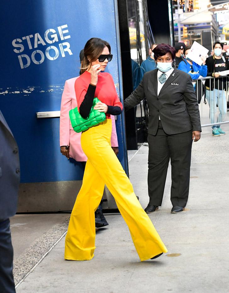 Виктория Бекхэм в желтых брюках и зеленой сумкой