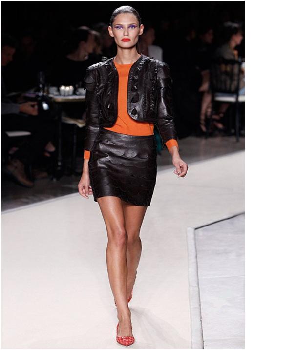 Девушка в черной кожаной юбке, черном кожаном жакете и оранжевой водолазке