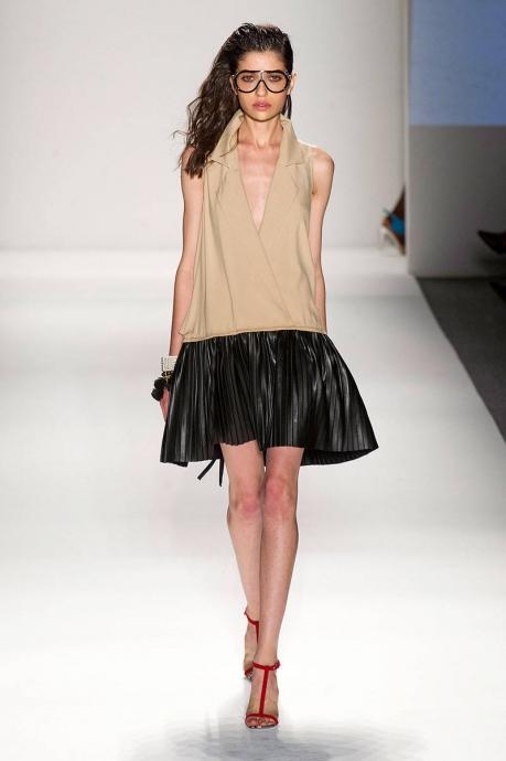 Девушка в черной кожаной юбке-клеш и бежевом открытом топе