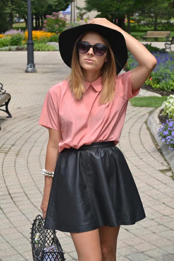 Девушка в черной кожаной юбке-клеш, розовой рубашке и с аксессуарами