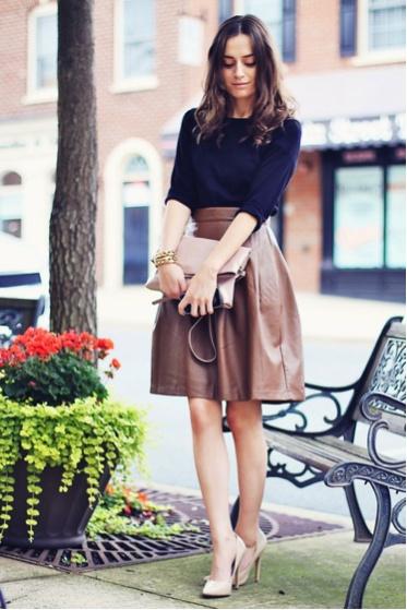 Девушка в длинной бежевой кожаной юбке, темном облегающем джемпере и нежно-бежевых туфлях