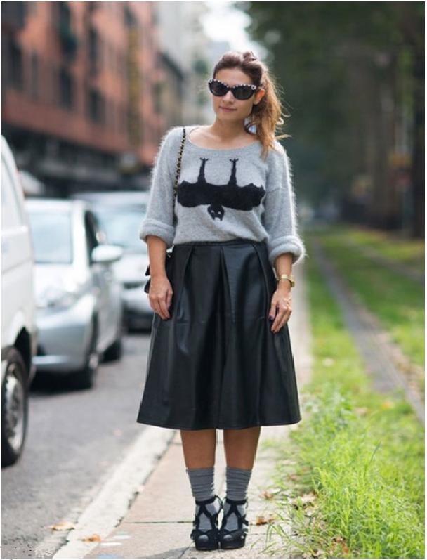 Девушка в длинной расклешенной кожаной юбке и сером топе с принтом