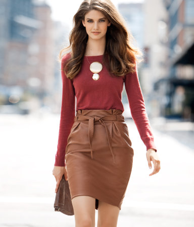 Девушка в коричневой кожаной юбке и бордовой водолазке