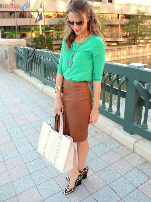 Девушка в коричневой кожаной юбке и зеленой рубашке