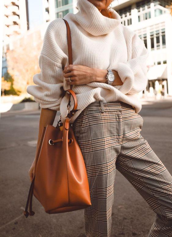 Девушка в брюках в клетку, белый свитер оверсайз и объемная коричневая сумка
